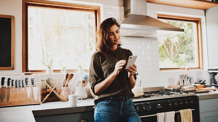 Cropped shot of an attractive young woman using a smartphone while standing in her kitchen at home.