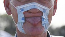 A participant in a demonstration protests on the Rhine meadows with a cut-up mask and tongue stuck out against the measures to combat the coronavirus in Duesseldorf, Germany, Sunday, Sept.20, 2020. (Roberto Pfeil/dpa via AP)