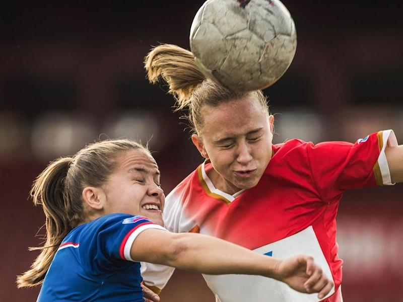 Determined teenage soccer players heading the ball on a match with their eyes closed: Getty