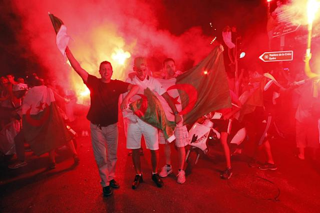 Algerian soccer fans cheer after their team qualified for the World Cup, in Marseille, southern France, Thursday, June 26, 2014. Algeria drew with Russia 1-1, and advanced to the round of 16 for the first time in their World Cup history. (AP Photo/Claude Paris)