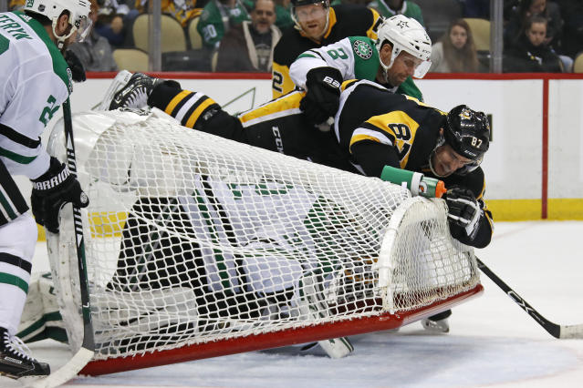 Dallas Stars' Dan Hamhuis (2) and Pittsburgh Penguins' Sidney Crosby (87) knock the goal cage on top of Stars' goaltender Kari Lehtonen during the second period of an NHL hockey game in Pittsburgh, Sunday, March 11, 2018. (AP Photo/Gene J. Puskar)
