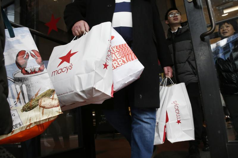 Shoppers leave Macy's in Boston, Friday, Nov. 29, 2019. Black Friday once again kicked off the start of the holiday shopping season. (AP Photo/Michael Dwyer)