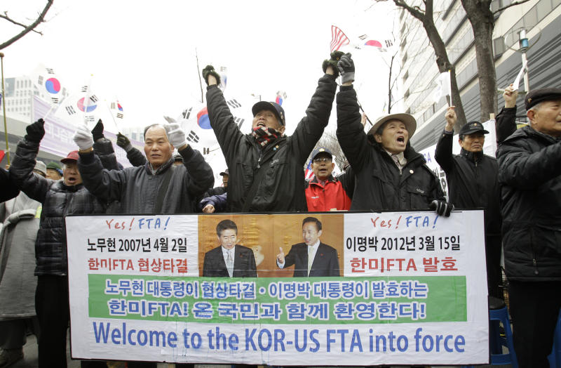 South Korean activists cheer to celebrate the free trade agreement, or FTA, with the United States during a rally near the U.S. Embassy in Seoul, South Korea, Wednesday, March 14, 2012. South Korea is implementing its long-stalled free trade deal with the United States about five years after the two countries struck the accord. South Korean trade officials say the pact aimed at slashing tariffs and other trade barriers is to take effect at midnight Wednesday. (AP Photo/Lee Jin-man)