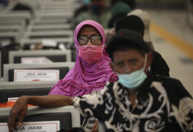 People wearing face masks sit spaced apart as a social distancing effort to help curb the spread of the coronavirus in a train station's waiting area, Tuesday, April 7, 2020, in Jakarta, Indonesia. The new coronavirus causes mild or moderate symptoms for most people, but for some, especially older adults and people with existing health problems, it can cause more severe illness or death. (AP Photo/Dita Alangkara)