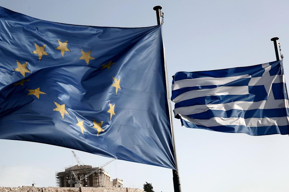 A Greek and a European Union flag billow in the wind as the ruins of the fifth century BC Parthenon temple is seen in the background on the Acropolis hill, in Athens, Friday, Jan. 23, 2015. (AP Photo/Petros Giannakouris)