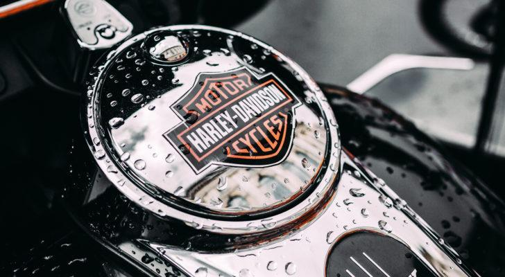 A close-up photograph of the tank to a Harley-Davidson motorcycle with raindrops on it.