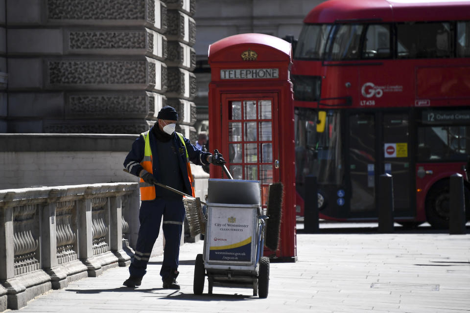 A council worker wearing a face mask to protect against coronavirus, collects refuse at Parliament Square, in London, Monday, May 18, 2020. Britain's Prime Minister Boris Johnson announced last Sunday that people could return to work if they could not work from home. (AP Photo/Alberto Pezzali)