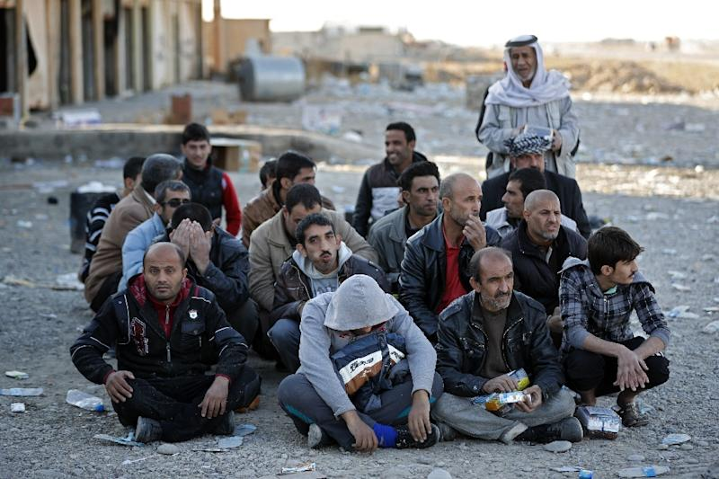 Displaced Iraqi families wait in Bartalla to be taken to a camp for displaced people (AFP Photo/Thomas Coex)