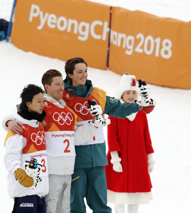<p>Gold medallist Shaun White of the U.S. flanked by silver medallist Ayumu Hirano of Japan and bronze medallist Scotty James of Australia during the flower ceremony. REUTERS/Jorge Silva </p>