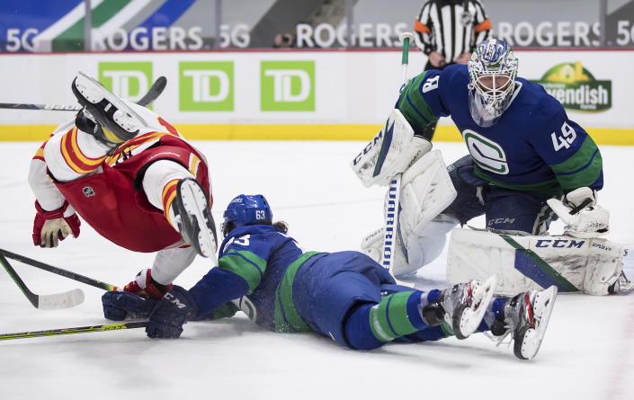 Calgary Flames' Milan Lucic, left, falls over Vancouver Canucks' Jalen Chatfield, center, after taking a shot on goalie Braden Holtby (49) during the third period of an NHL hockey game, Sunday, May 16, 2021, in Vancouver, British Columbia. (Darryl Dyck/The Canadian Press via AP)