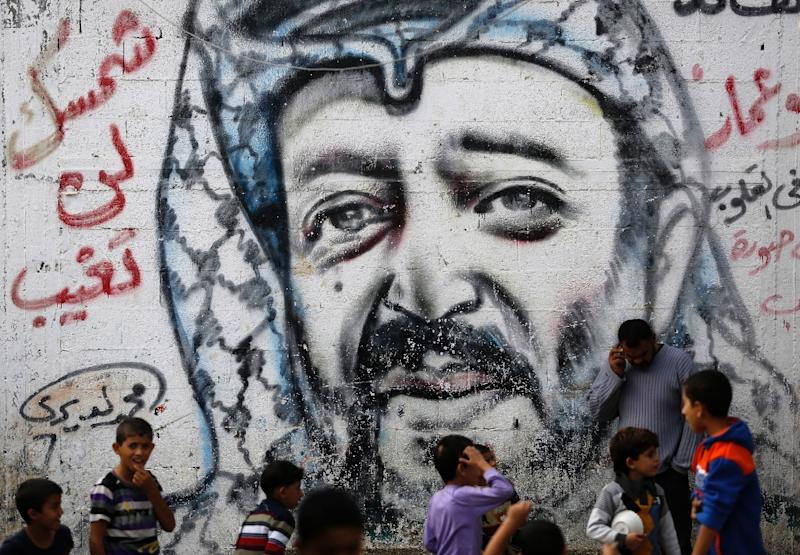 Palestinian children play in front of a mural of late nationalist leader Yasser Arafat in the Al-Shati refugee camp in Gaza City (AFP Photo/MOHAMMED ABED)