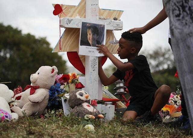 <p>Nekhi Charlemagne writes a message on a cross setup in a makeshift memorial in front of Marjory Stoneman Douglas High School on February 19, 2018 in Parkland, Florida. (Photo: Joe Raedle/Getty Images) </p>