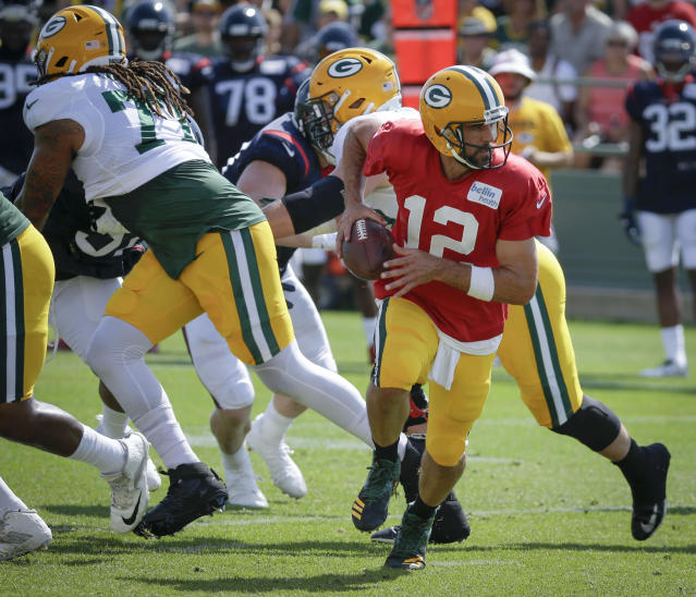 Green Bay Packers quarterback Aaron Rodgers (12) prepares to hand off the football during a joint NFL football practice with the Houston Texans, Monday, Aug 5, 2019, in Green Bay, Wis. (AP Photo/Mike Roemer)