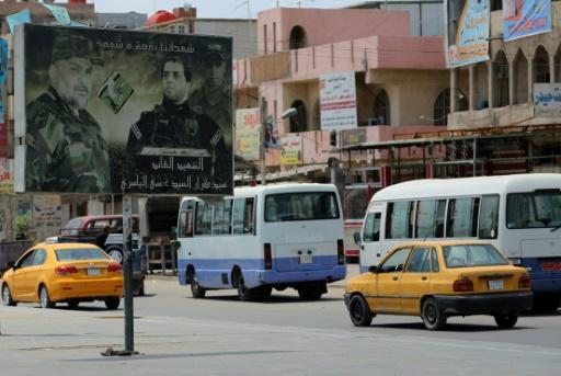 Traffic and an election poster on a road in Sadr City, the impoverished stronghold in northeast Baghdad of Iraqi cleric Moqtada Sadr