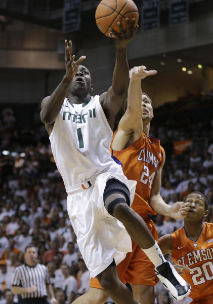 Miami's Durand Scott (1) slides past Clemson's Milton Jennings (24) for a basket during the first half of a NCAA college basketball game in Coral Gables, Fla., Saturday, March 9, 2013. (AP Photo/J Pat Carter)