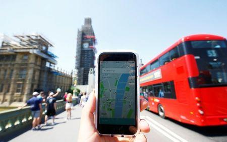 A photo illustration shows the Uber app and a bus in London