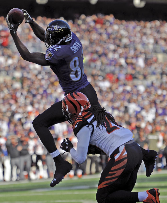 Baltimore Ravens wide receiver Torrey Smith, top, pulls in a touchdown pass as he is hit by Cincinnati Bengals free safety Reggie Nelson during the first half of an NFL football game in Baltimore, Sunday, Nov. 10, 2013. (AP Photo/Nick Wass)