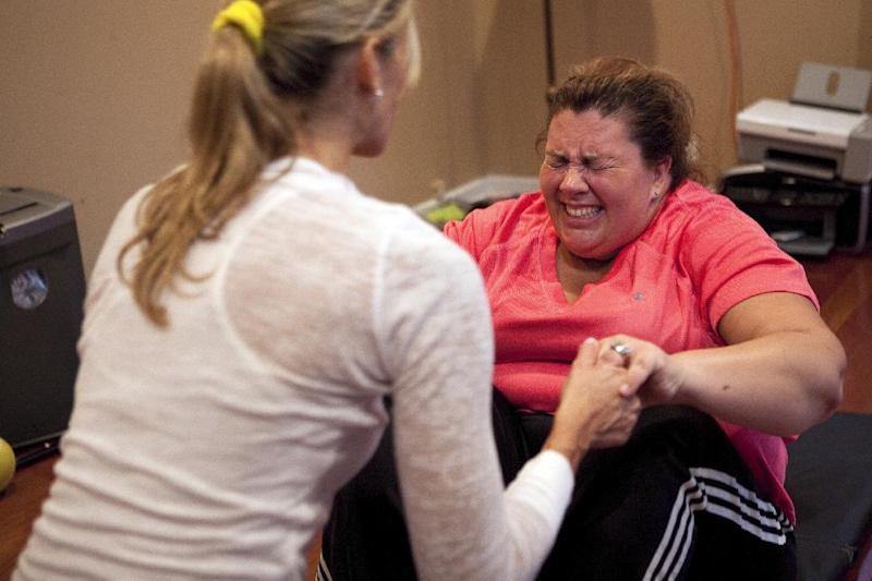 "This Monday, Oct. 10, 2011 photo courtesy of Food Network shows caterer Ally Vitella, right, as she does modified sit ups with the assistance of health consultant Christine Avanti, during a workout at the Vitella residence in North Caldwell, N.J., as seen on Food Network's ""Fat Chef."" Vitella dropped from a size 28 to a size 16 during the show. (AP Photo/Food Network)"