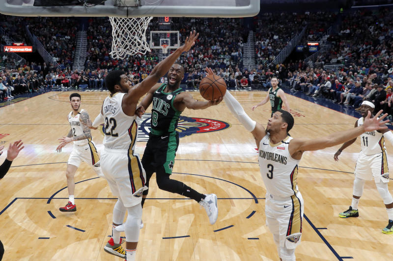 Boston Celtics guard Kemba Walker (8) goes to the basket between New Orleans Pelicans center Derrick Favors (22) and guard Josh Hart (3) in the first half of an NBA basketball game in New Orleans, Sunday, Jan. 26, 2020. (AP Photo/Gerald Herbert)