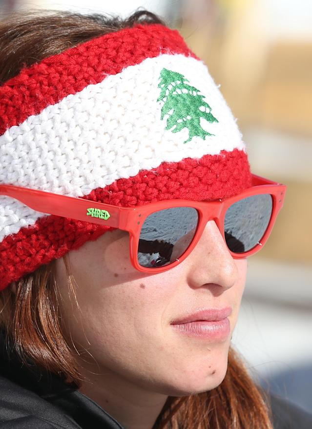 """Lebanon's Jacky Chamoun sits near the alpine ski course finish area at the Sochi 2014 Winter Olympics, Thursday, Feb. 13, 2014, in Krasnaya Polyana, Russia. The Lebanese Olympic skier seen topless in revealing photographs and a video that circulated on the Internet says her country's sports officials are """"on my side."""" Three years ago, Chamoun posed for a calendar photo shoot. Behind-the-scenes footage recently was posted online, and Lebanon's Sports and Youth Minister reportedly ordered an investigation. (AP Photo/Luca Bruno)"""