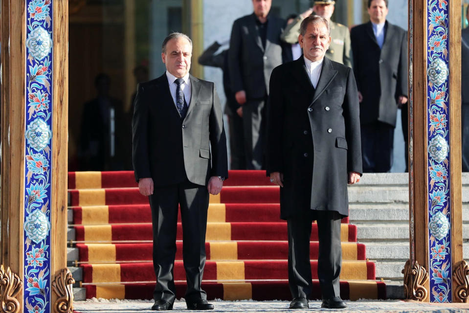 In this photo released by official website of the Office of the Iranian Vice President, Syrian Prime Minister Imad Khamis, left, welcomed by Iranian Senior Vice-President Eshaq Jahangiri during his official arrival ceremony at the Saadabad Palace in Tehran, Iran, Monday, Jan. 13, 2020. (Office of the Iranian Vice President via AP)