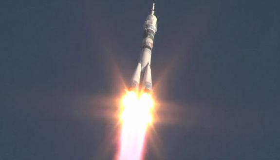 A Russian Soyuz rocket launches toward space carrying the Olympic torch for the 2014 Sochi Winter Olympics and the new Expedition 38 crew for the International Space Station at 11:14 p.m. EST on Nov. 6, 2013. The rocket carrying Expedition 38 f