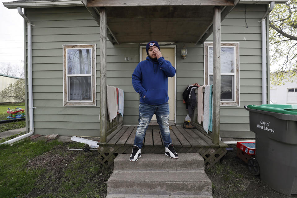 Omar Martinez talks about how the coronavirus has affected his family as he stands on the front porch of the family home, Saturday, April 25, 2020, in West Liberty, Iowa. (AP Photo/Charlie Neibergall)