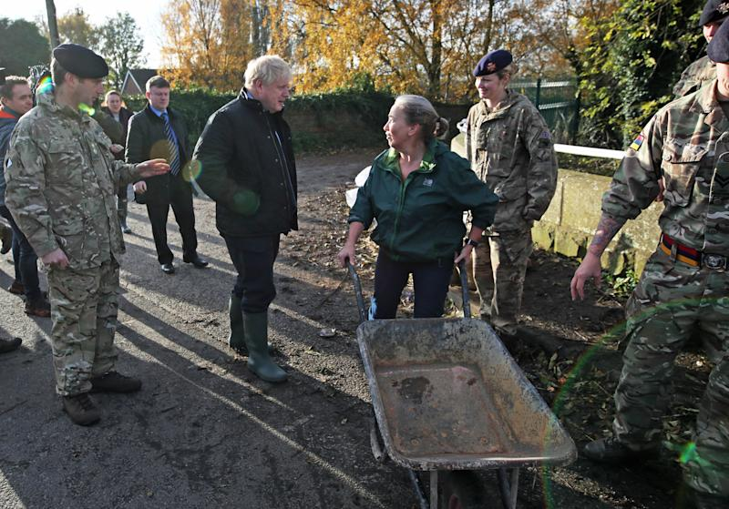Prime Minister Boris Johnson talks with a local woman pushing a wheelbarrow during a visit to Stainforth, Doncaster, to see the recent flooding.
