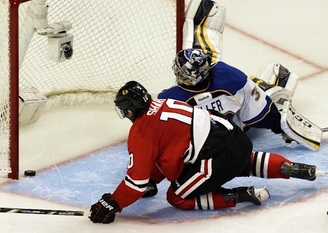Chicago Blackhawks' Patrick Sharp (10) scores against St. Louis Blues goalie Ryan Miller (39) during the third period in Game 6 of a first-round NHL hockey playoff series in Chicago, Sunday, April 27, 2014. The Blackhawks won 5-1. (AP Photo/Nam Y. Huh)