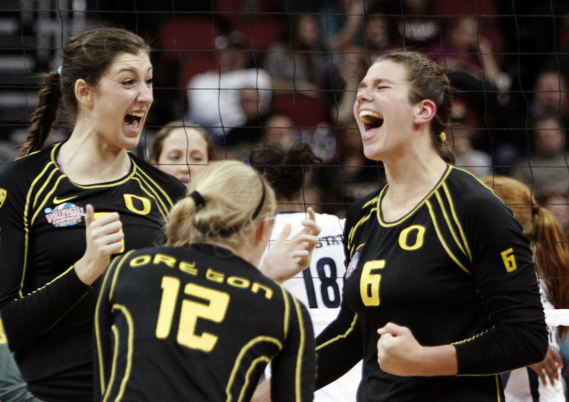 FILE - In this Dec. 13, 2012, file photo, Oregon's Canace Finley, left, Katherine Fischer (12) and Liz Brenner (6) celebrate a second game victory over Penn State in the national semifinals of the NCAA college women's volleyball tournament in Louisville, Ky. Brenner figures she's only in college once, she might as well play the sports she loves. And for the Oregon sophomore, that's volleyball, basketball, softball and track and field — although not at once. (AP Photo/Garry Jones, File)