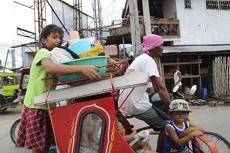 Residents with their belongings ride on a tricycle cab to an evacuation center in Tacloban city, central Philippines December 4,  2014. REUTERS/Stringer