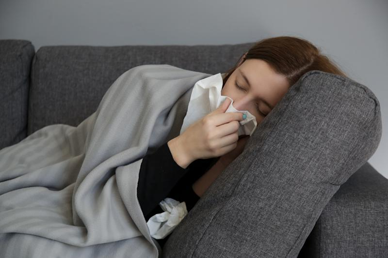 Young woman on the sofa blowing nose into a white paper tissue. Studio shot of young woman with allergy symptoms sneezing into a tissue. Flu, cold or allergy symptom.