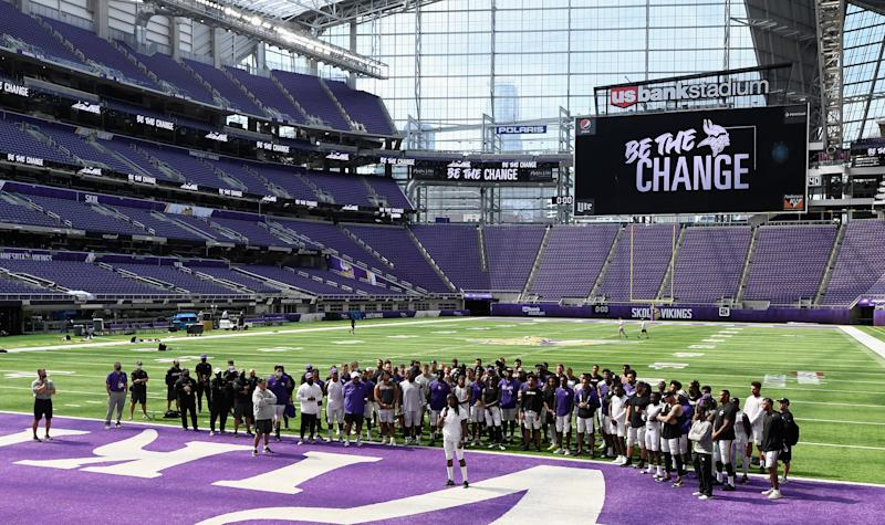 "Minnesota Vikings stadium with players huddled near end zone and ""Be The Change"" on the videoboard."