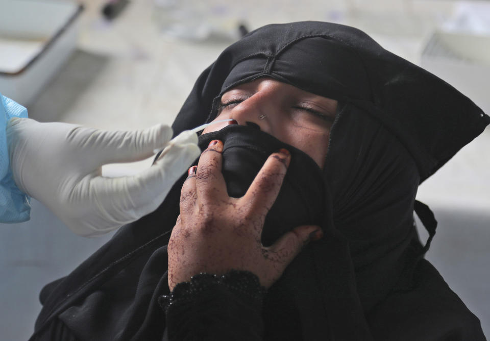 A health worker takes a nasal swab sample at a COVID-19 testing center in Hyderabad, India, Saturday, Oct. 3, 2020. India has crossed 100,000 confirmed COVID-19 deaths on Saturday, putting the country's toll at nearly 10% of the global fatalities and behind only the United States and Brazil. (AP Photo/Mahesh Kumar A.)