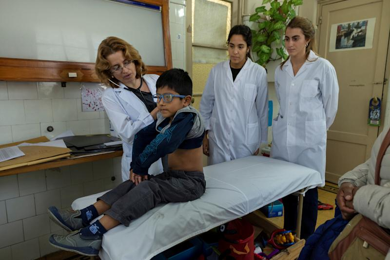 "Brigida Simaniz (not pictured) watches over her son Nicholas, 7, as he is examined by Dr Laura Lagrutta, a pulmonologist specialising in children with tuberculosis, at Dr. Raul Vaccarezza Institute in Buenos Aires, Argentina March 26, 2019. Brigida Simaniz finished her TB treatment earlier this year in May. She works in a textile workshop on 70 pesos ($1.19) an hour and lives with her two children in the shantytown of Bajo Flores, all three sharing the same bed. Her fear was passing the infection to her kids. ""I was scared when they told me the diagnosis because I did not know it existed. I always followed the treatment as the doctors said for fear of infecting my children,"" said Simaniz. ""Even though it was cold at night, I opened the windows of the room to circulate the air."" (Photo: Magali Druscovich/Reuters)"