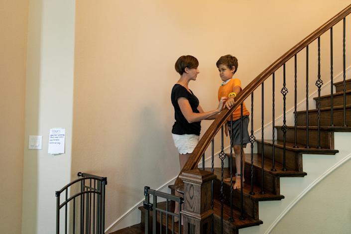 Rachel Scott helps her son Braden walk down the stairs in their home. | Ilana Panich-Linsman for TIME