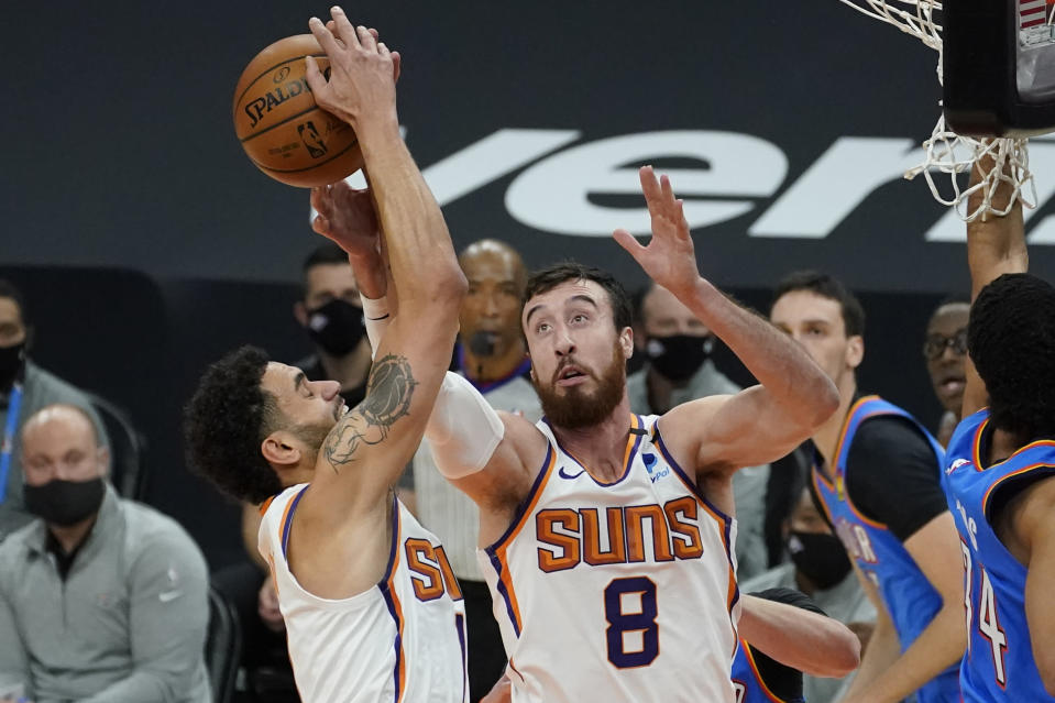 Phoenix Suns forward Frank Kaminsky (8) and forward Abdel Nader battle for a rebound against the Oklahoma City Thunder during the first half of an NBA basketball game, Wednesday, Jan. 27, 2021, in Phoenix. (AP Photo/Matt York)
