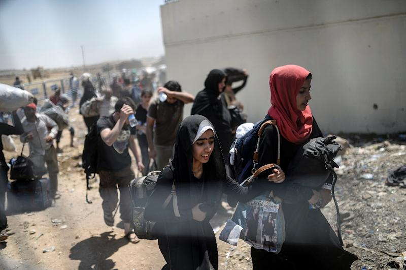Syrians fleeing the conflict walk towards the Turkish border at the Akcakale crossing in Sanliurfa province, on June 15, 2015 (AFP Photo/Bulent Kilic)