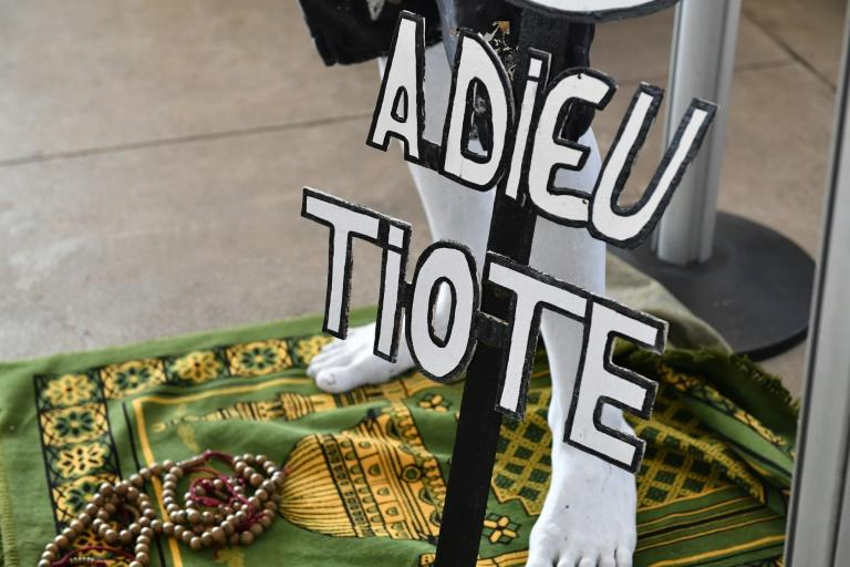 "A supporter holding a sign reading ""Farewell Tiote"" attends the arrival of the casket of the late Ivory Coast midfielder Cheick Tiote, on June 15, 2017 upon its arrival from China at Abidjan's airport, prior to his funeral ceremony"