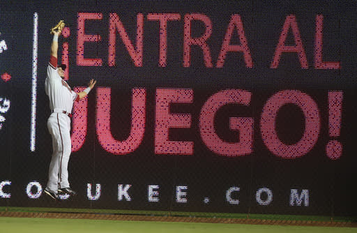 "Arizona Diamondbacks right fielder David Peralta catches a fly ball hit by Miami Marlins' Garrett Jones during the second inning of a baseball game in Miami, Thursday, Aug. 14, 2014. The billboard urges players to ""get in the game'. (AP Photo/J Pat Carter)"