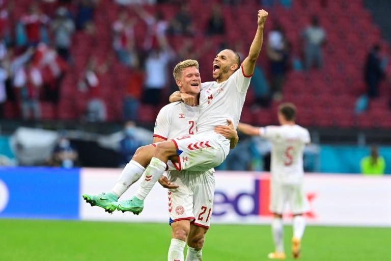 Martin Braithwaite is cradled by teammate Andreas Cornelius after scoring Denmark's fourth goal against Wales