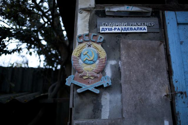 """In this photo taken on Wednesday, Nov. 27, 2013, the colored state emblem of the USSR hangs on the door of the outhouse in the yard of the railroad house in the village of Vesyoloye outside Sochi, Russia. Signs read """"Chief engineer; Showers."""" As the Winter Games are getting closer, many Sochi residents are complaining that their living conditions only got worse and that authorities are deaf to their grievances. (AP Photo/Alexander Zemlianichenko)"""