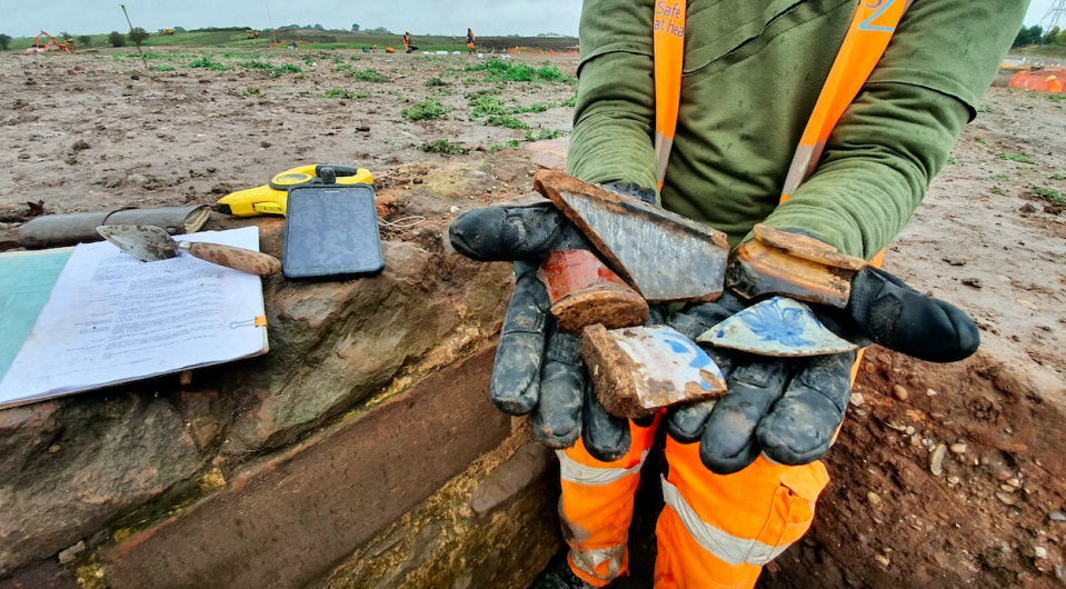 A Wessex archaeologist shows post medieval pottery from the Coleshill Medieval Manor site. (SWNS)