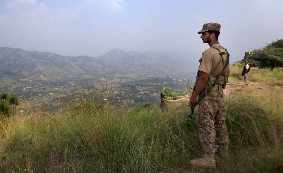 FILE- In this Oct. 1, 2016, file photo, Pakistan army soldiers monitor the area from the hilltop Bagsar post on the line of control, that divides Kashmir between Pakistan and India, near Bhimber, some 166 kilometers (103 miles) from Islamabad, Pakistan. The highly militarized de facto border that divides the disputed region between the two nuclear-armed rivals India and Pakistan, and a site of hundreds of deaths, is unusually quiet after the two South Asian neighbors agreed in February, 2021, to reaffirm their 2003 cease-fire accord. (AP Photo/Anjum Naveed, File)