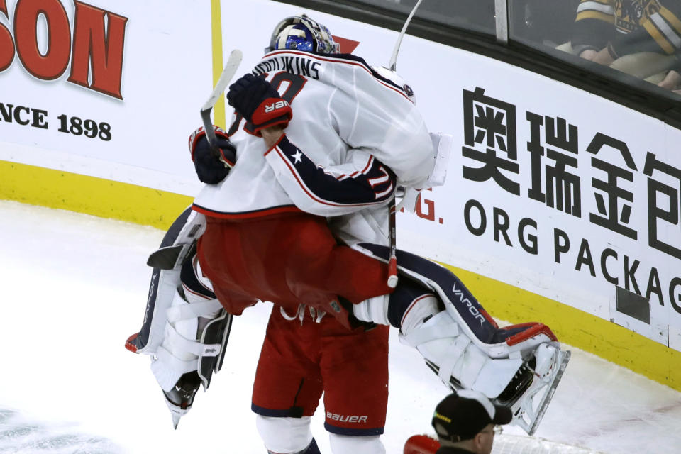 Columbus Blue Jackets goaltender Elvis Merzlikins (90) jumps into the arms of teammate Nick Foligno (71) to celebrate their victory over the Boston Bruins in the overtime period of an NHL hockey game, Thursday, Jan. 2, 2020, in Boston. (AP Photo/Elise Amendola)