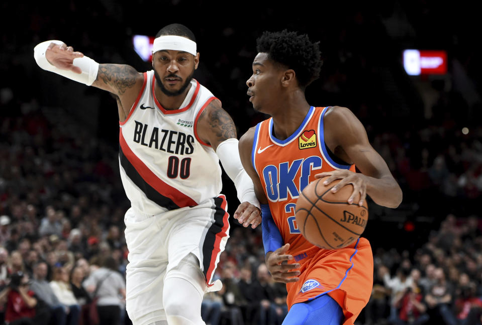 Oklahoma City Thunder guard Shai Gilgeous-Alexander, right, drives to the basket on Portland Trail Blazers forward Carmelo Anthony, left, during the first half of an NBA basketball game in Portland, Ore., Sunday, Dec. 8, 2019. (AP Photo/Steve Dykes)