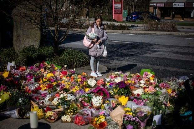 People placed flowers at a memorial outside the Lynn Valley Library for the victims of a mass stabbing incident that took place on Saturday in North Vancouver. (Ben Nelms/CBC - image credit)