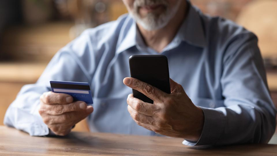 Close up mature man using phone, holding plastic credit or debit card, senior grey haired customer making secure internet payment, shopping or browsing online banking service, entering information