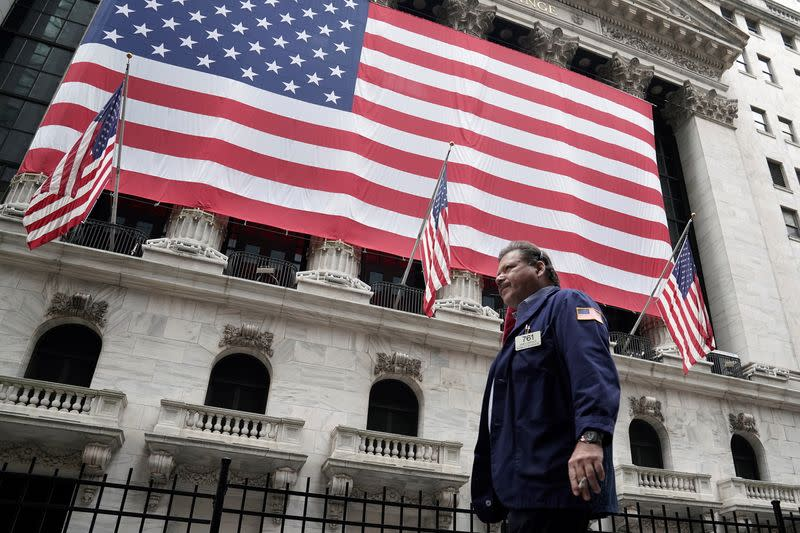 A trader walks past the New York Stock Exchange in the Manhattan borough of New York City