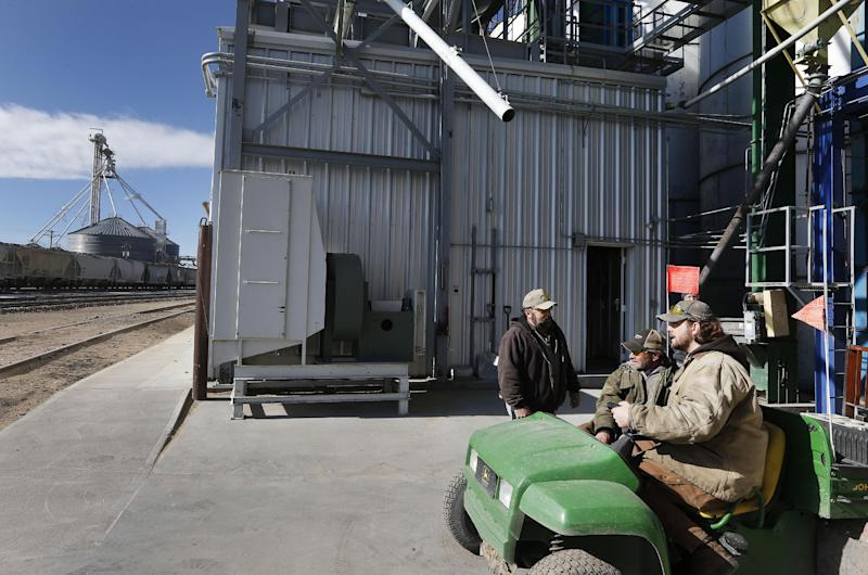 In this Nov. 6, 2013 photo, workers, left to right, Dan Dannar, Jeff Brown, and Kevin Orr talk at Global Harvest Foods, which produces birdseed and other grains, in the rural town of Akron, the county seat of Washington County, Colo. A day earlier, a majority in Washington and four other counties on Colorado's Eastern Plains voted yes on the creation of a 51st state, largely over residents' alienation from voters statewide on issues such as civil unions for gay couples, new renewable energy standards, and limits on ammunition magazines. (AP Photo/Brennan Linsley)